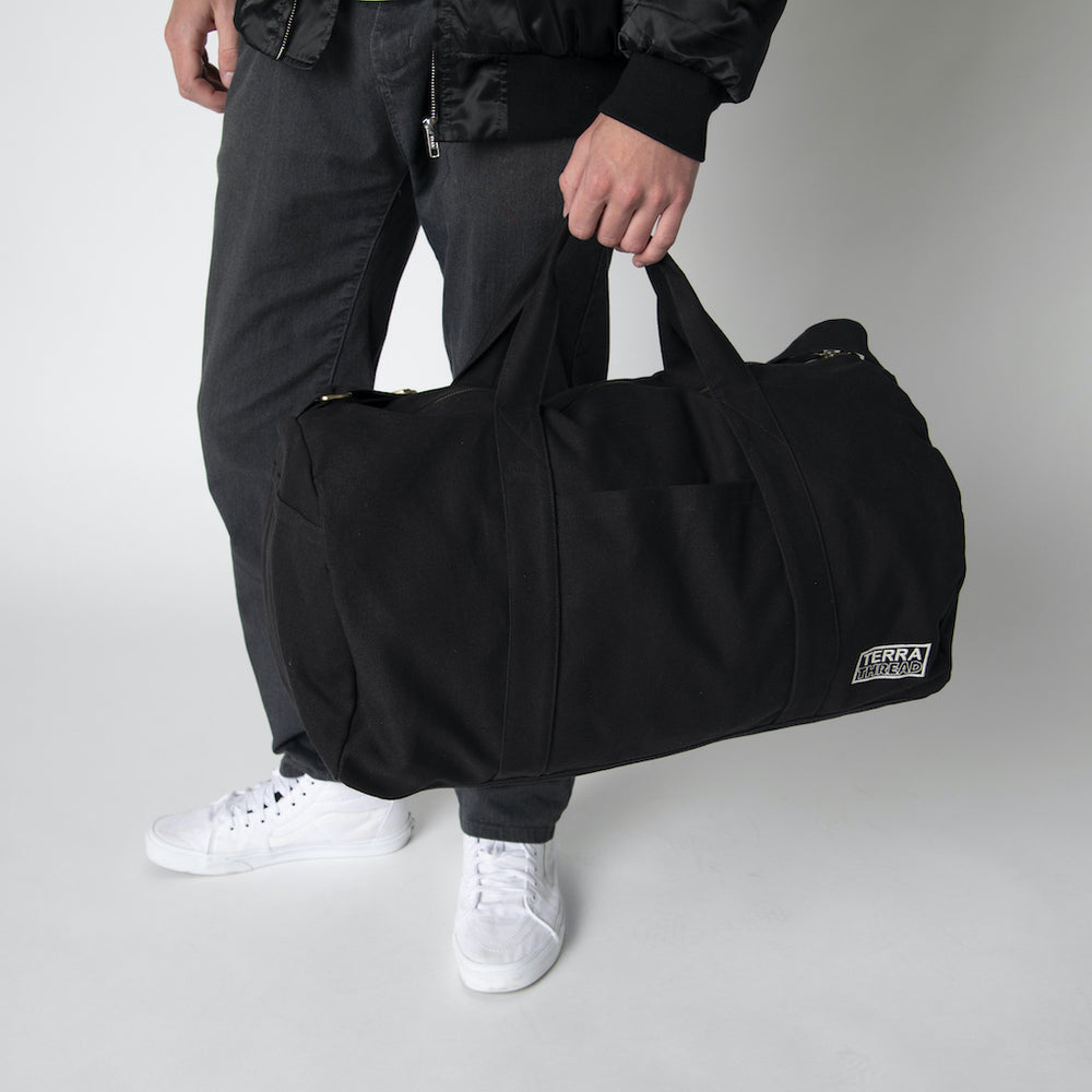 A male model holding a black canvas duffle bag from Terra Thread