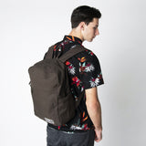 A male model wearing a brown Terra Thread organic cotton backpack