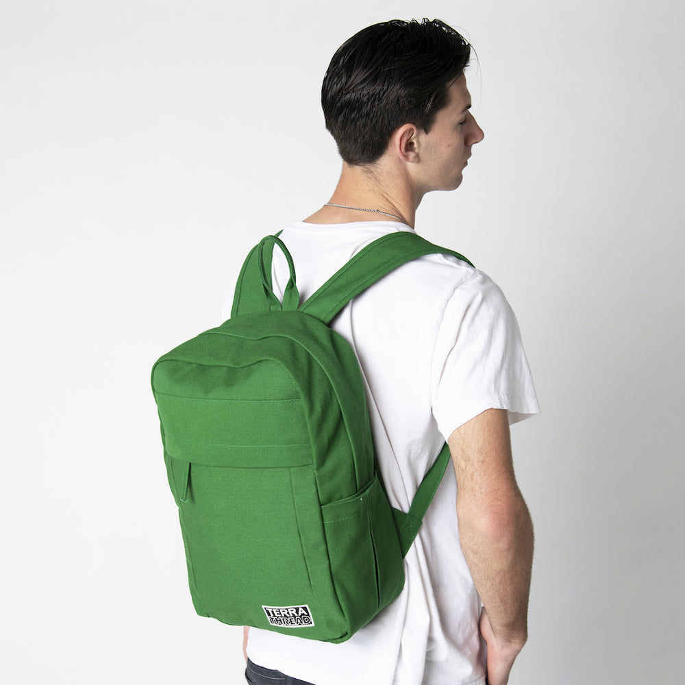 A male model wearing a Terra Thread green canvas backpack