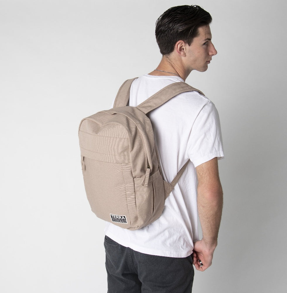 A male model wearing a Terra Thread neutral color backpack