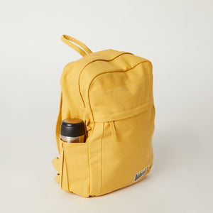 Side view of a Terra Thread yellow canvas backpack