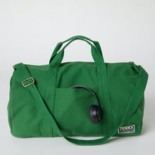 Load image into Gallery viewer, A green organic cotton duffle bag with headphones in the front pocket