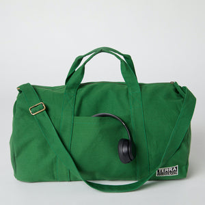 A green organic cotton duffle bag with headphones in the front pocket