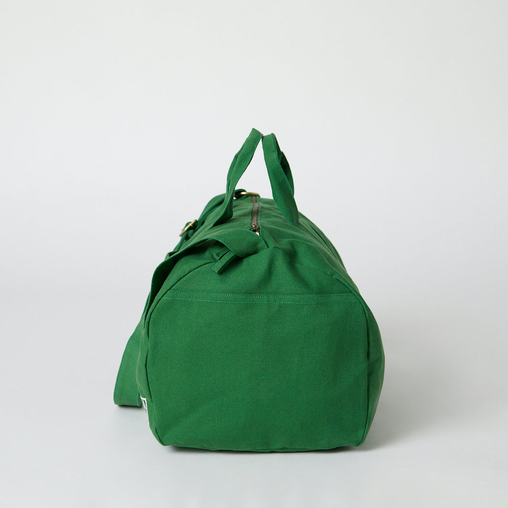 A side view of a green  color organic duffle bag