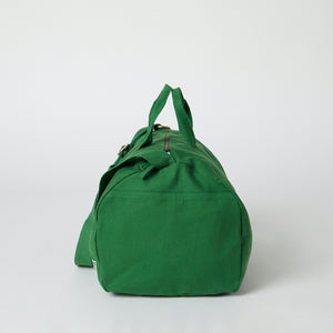 A side view of a green organic duffle bag
