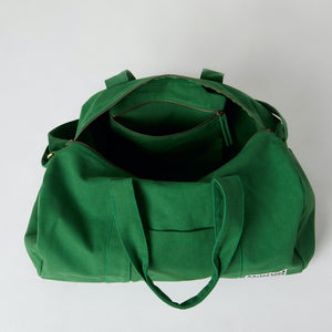 Inside pocket view of a green organic cotton duffle bag