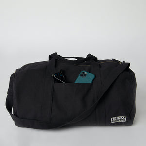 A black canvas duffle bag with an iPhone in the front pocket