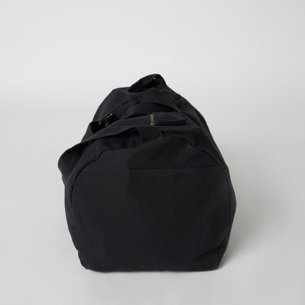 A side view of a black cotton  canvas duffle bag