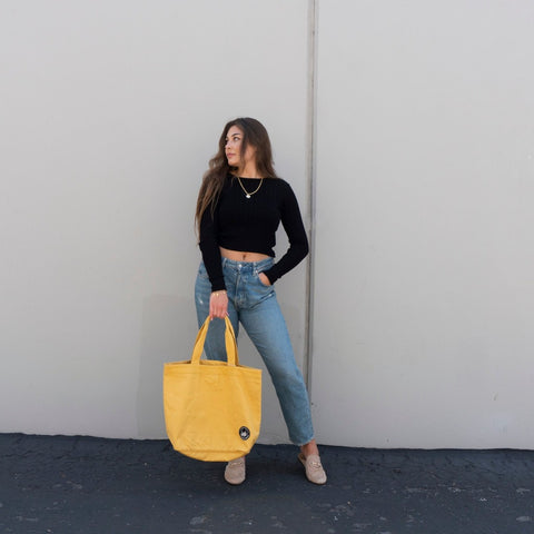 Model carrying a yellow tote bag made with organic cotton below her waist