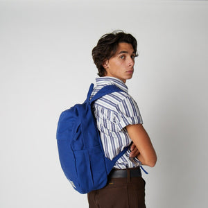 A male model wearing a blue cotton backpack over the shoulder