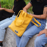 Model carrying a yellow tote bag made with organic cotton on her right shoulder