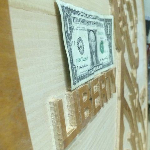 oversized penny cut from plywood close up with actual dollar bill for size reference
