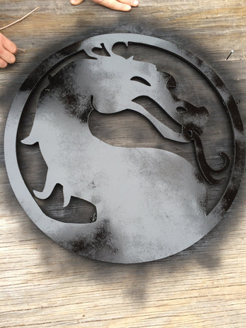 mortal kombat logo cut from mdf with one coat of black spray paint