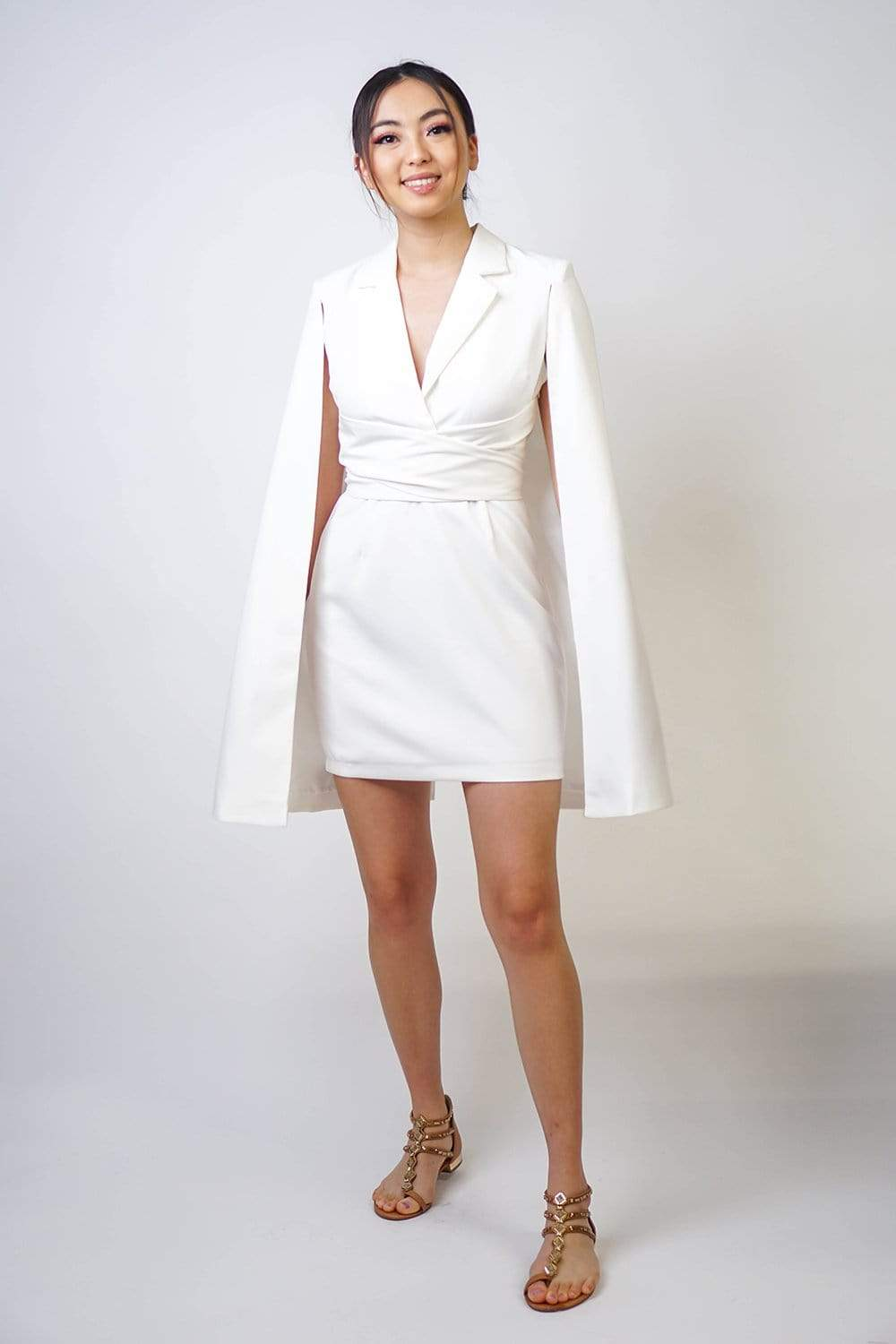 V-neck notch collar tailored white dress with a sewn on cape that will add some drama to your look. Slightly padded at the shoulders with a wrapped waistline to accentuate the figure.