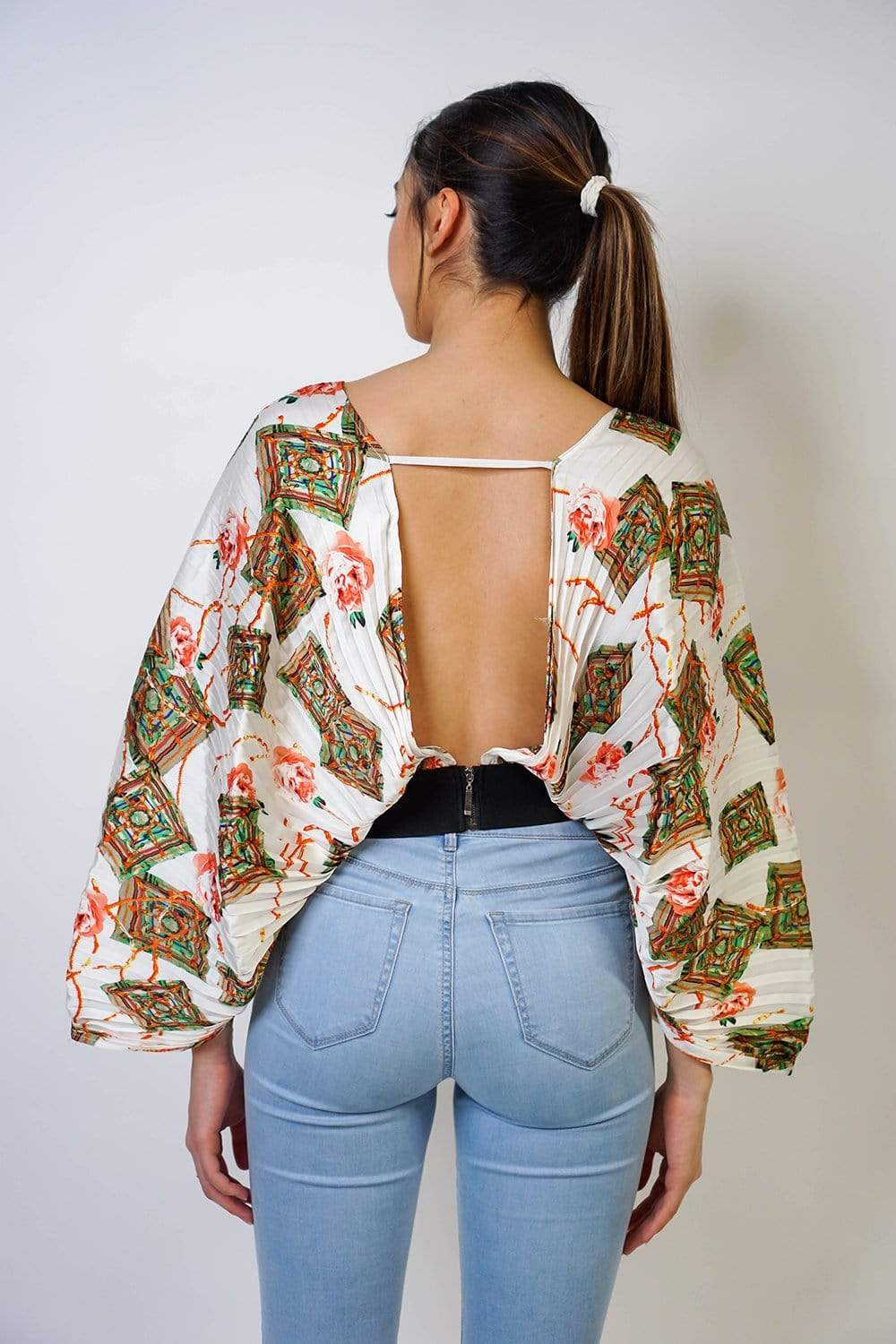 Pleated kimono sleeve crop top. Open back and V-neck to give it a more sexy look. With its cream floral colors is perfect for daytime and nightime outfits. Elastic black waistline to maintain its shape. Wear it with some jeans for a casual look or with a black skirt our black loose pants for a more elegant look.