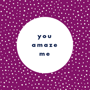"5"" x 5"" laminated card. Purple background with white dot patters. White circle in the middle with ""you amaze me"" in navy blue bold lowercase san serif text."