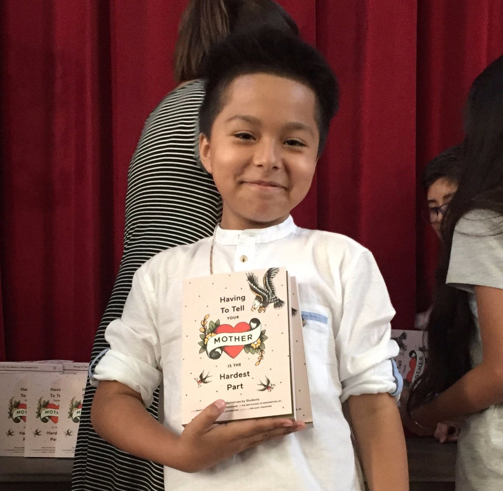 Young Latino boy holds a copy of the book to his chest on his right.