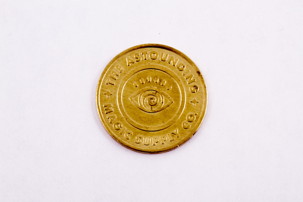 Quarter-sized gold coin. Eye on one side. Cross wands on the other side. Tivoli's logo on both sides.