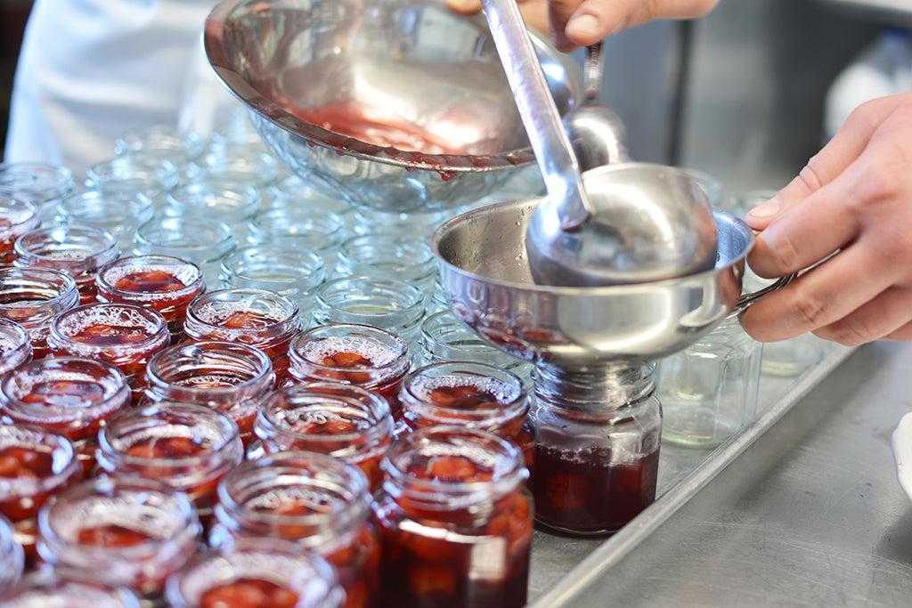 Filling preserves by hand with a ladle and funnel at Quince and Apple