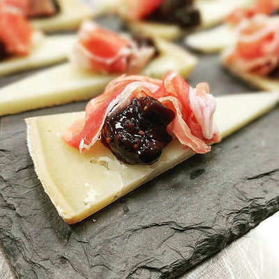 Figs and Black Tea with prosciutto on a piece of gruyere cheese
