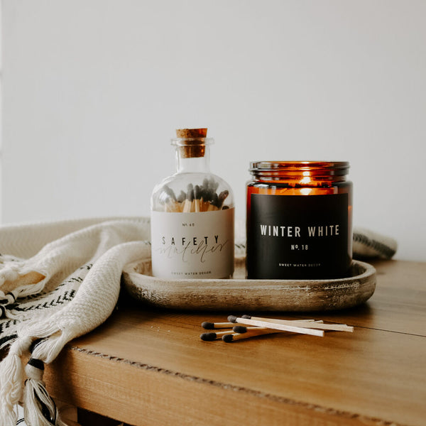 Amber jar soy candle and match bottle sitting on a rustic wood tray.