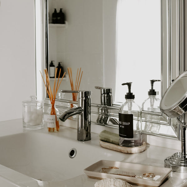 Bathroom vanity styled with a reed diffuser, refillable hand soap dispenser, and a rustic wood tray.