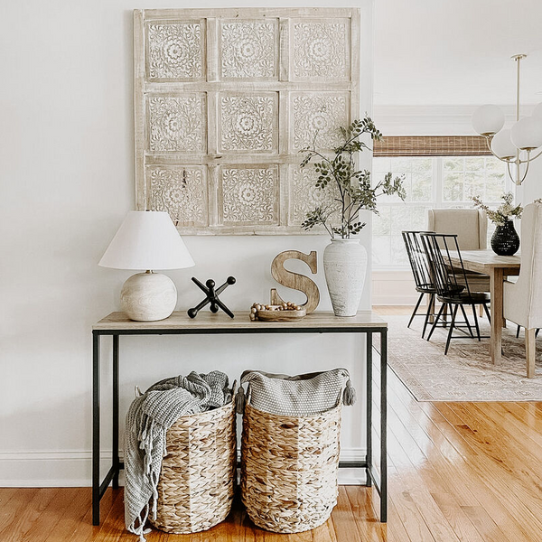 Entry table styled with a beige lamp, decorative wood try, and other neutral home decor items.