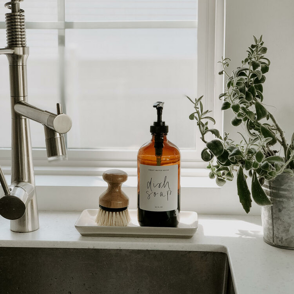 Amber jar dispenser bottle and a kitchen brush scrubber styled on a decorative ceramic tray on a kitchen sink.