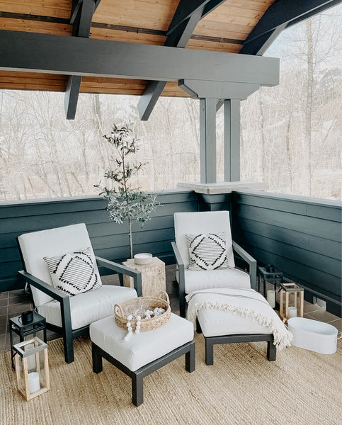 Modern farmhouse style covered outdoor patio with two accent chairs and a throw blanket