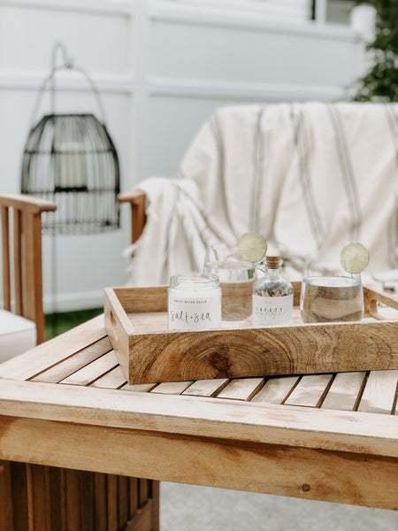 Outdoor living area with a decorative tray, soy wax candle, safety matches, and lemon water.