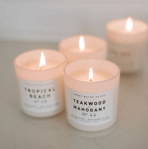 White jar soy wax candles from sweet water decor in Teakwood and Mahogany and Tropical Beach scents.