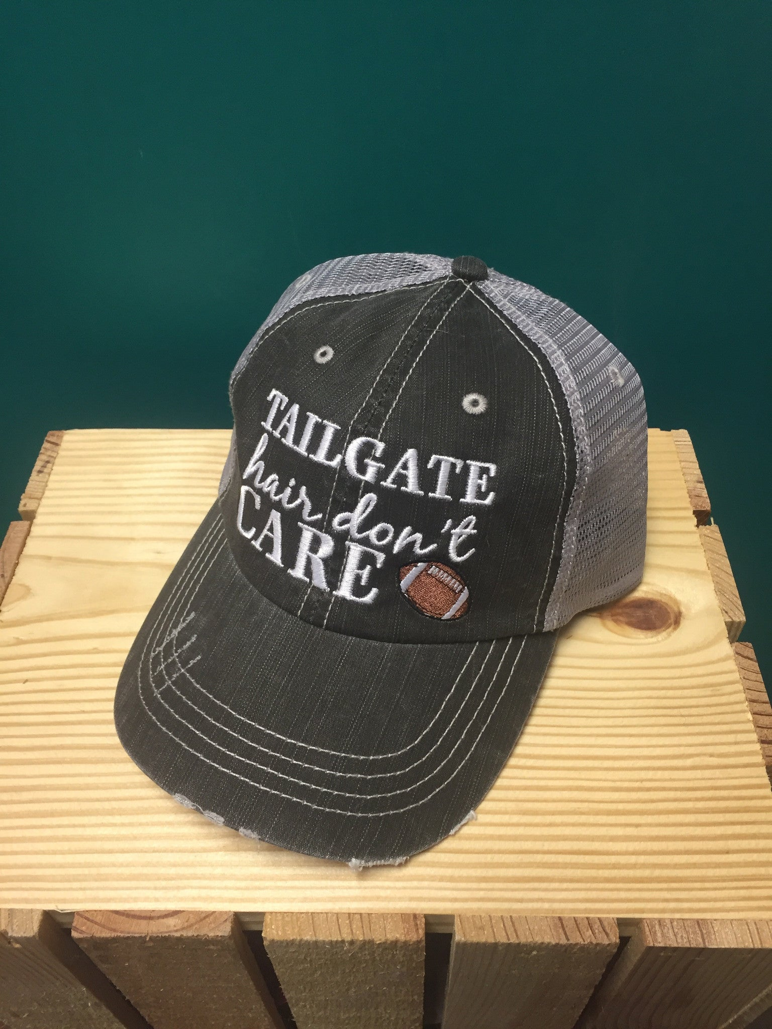 "black baseball cap with the words ""tailgate hair don't care"" with a football on it"