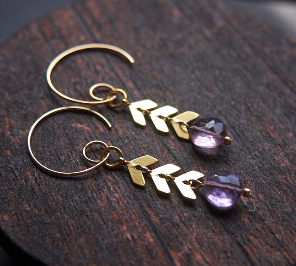 Modern amethyst earrings with gold chevron chain detail on a wooden background