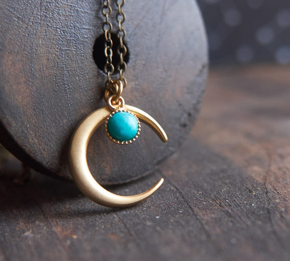 Matte gold half moon necklace with delicate turquoise accent displayed with dark brass chain