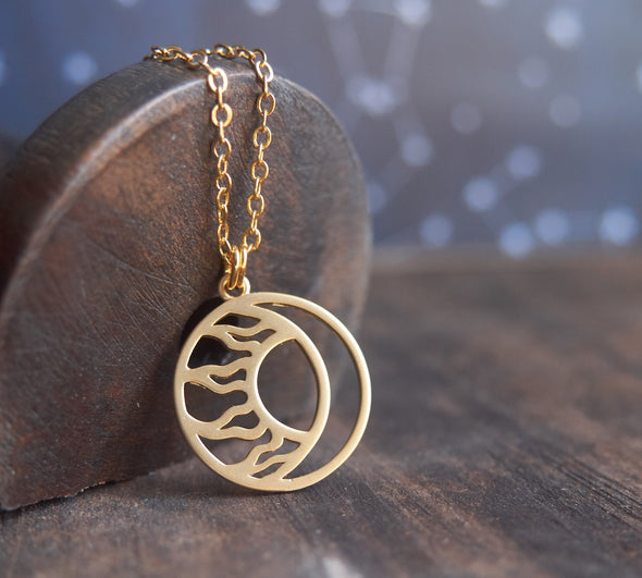 Matte gold moon and sun circle necklace resting on wood spool