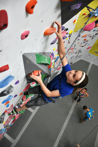 young girl rock climbing on a rope