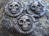 3 silver colored skull pins