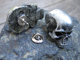 silver colored skull pin