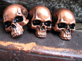 3 copper colored skull pins