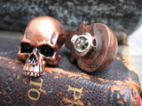 2 copper colored skull pins