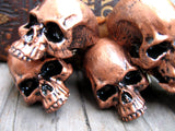 many copper colored skull pins