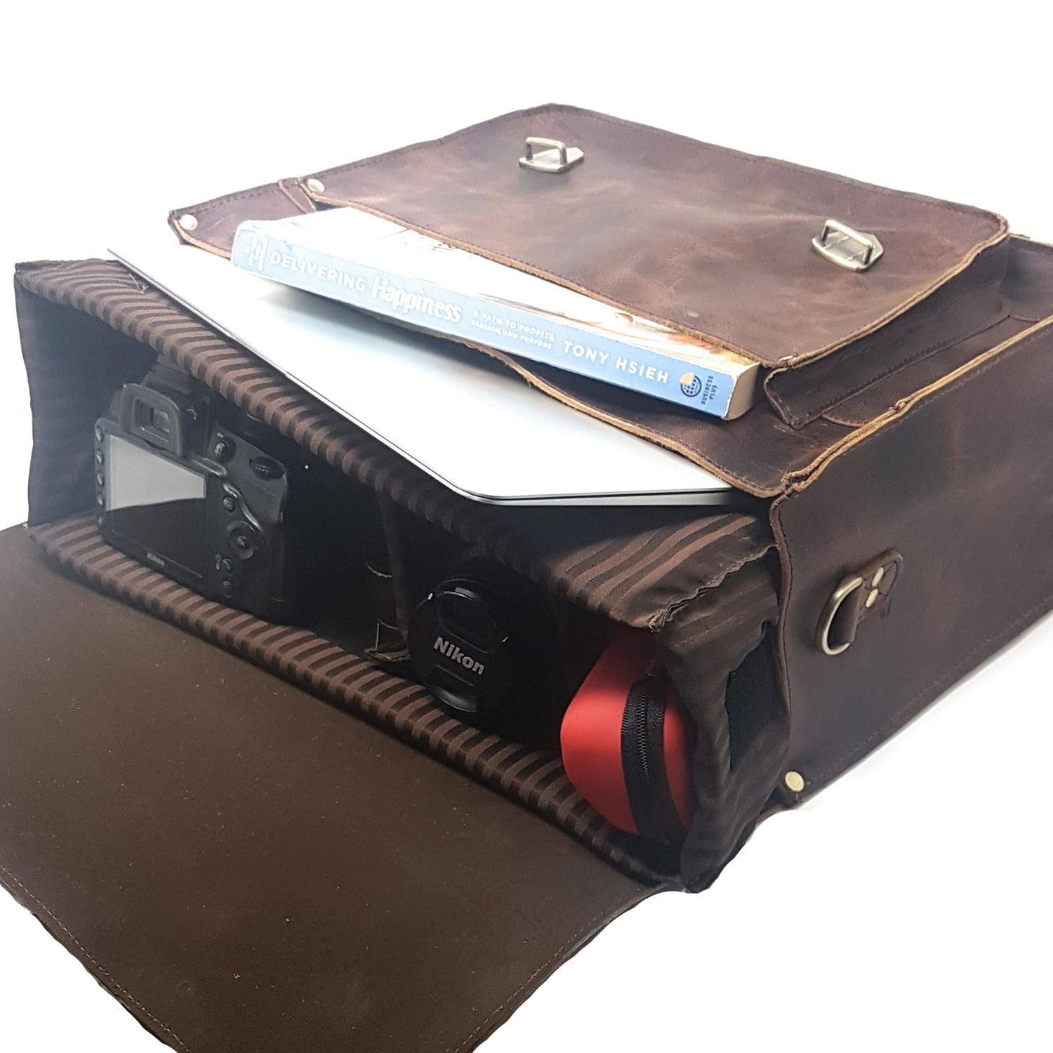 brown leather camera bag interior with DSLR body, lens, MacBook laptop, book, sunglasses, padded case