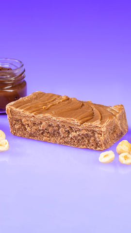 Nutella Fudge Piece Surrounded by Hazelnuts and a Clear Jar of Nutella