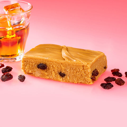Handmade Fudge with Pink Background surrounded by a glass of rum