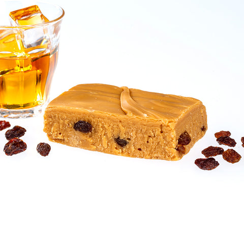 Handmade Fudge Surrounded by A clear glass of rum and raisins
