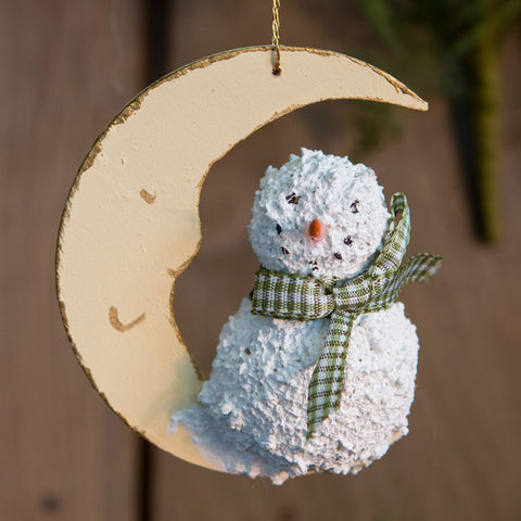 A moon and snowman Christmas tree ornament.