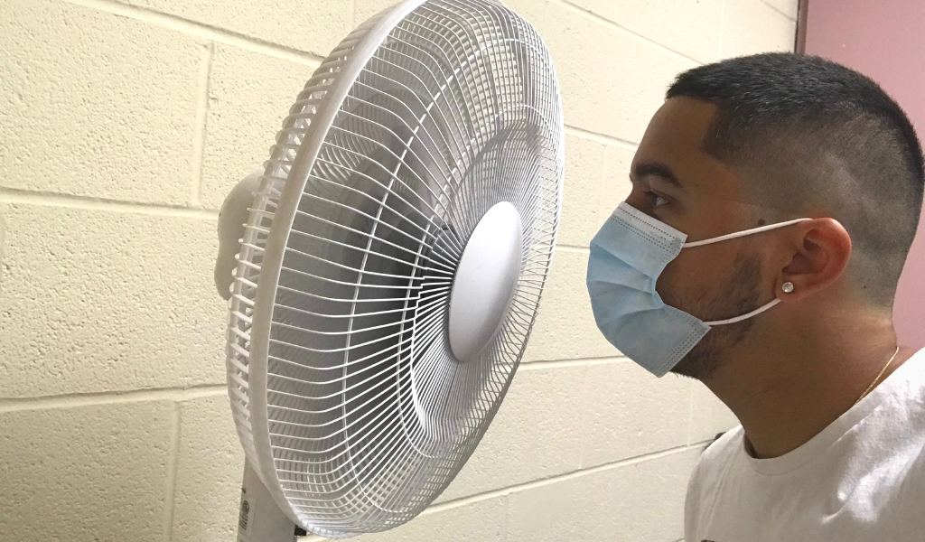 man wearing face mask standing in front of a fan