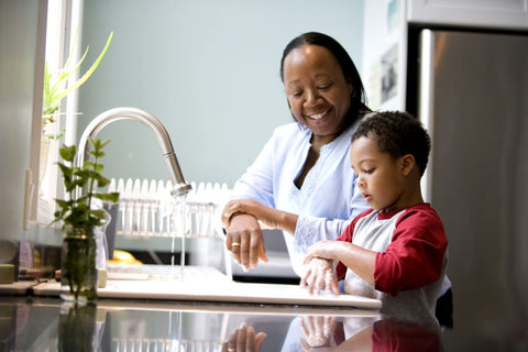 Mother teaching her young son how to wash hands at kitchen sink. Mother is wearing a light blue long sleeve shirt and son is wearing red and grey long sleeve.