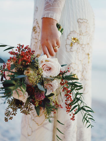bride stands in a white wedding dress holding a flower bouquet