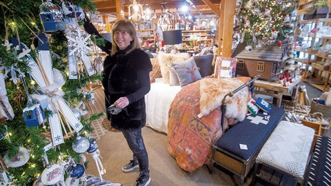 Kate Carpenter stands with a Christmas tree at Stowe Kitchen Bath and Linens